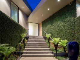 Vstup do domu roubí pěstěnou zelení obrostlé stěny