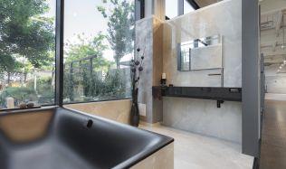 Stylové koupelny plné inspirace - Imitace světlého mramoru s černou vanou a umyvadlem