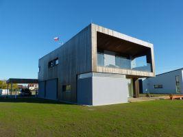 Kompaktní tvar a stínění velkých oken přesahem střechy
